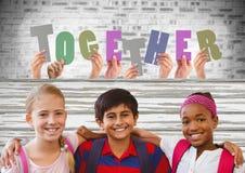 Lettere insieme insieme tagliate con gli amici dei bambini davanti al muro di mattoni Fotografia Stock Libera da Diritti