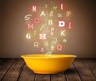 Lettere variopinte che escono a casa dalla ciotola di minestra del cuoco fotografia stock libera da diritti