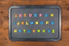 Lettere variopinte della schiuma sulla lavagna Fotografia Stock