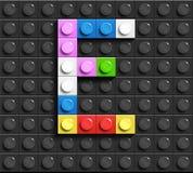 Lettere variopinte E dell'alfabeto dai mattoni di lego della costruzione sul fondo nero del mattone di lego fondo di lego lettere illustrazione di stock