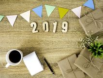 Lettering 2019 and all sorts of stationery items on the wooden surface. royalty free stock images
