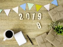 Lettering 2019 and all sorts of stationery items on the wooden surface royalty free stock photo