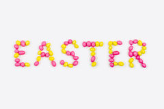 Lettering «Easter» is made with  candies. Lettering «Easter» is made with pink and yellow candies  on white background Stock Photos
