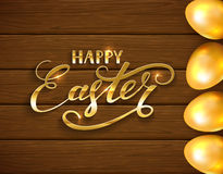 Lettering Happy Easter and golden eggs on brown wooden background Royalty Free Stock Photo