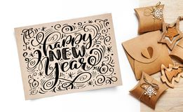 Lettering Happy New Year greeting card - text in vintage kraft paper on a white background. Flat lay, top view photo Royalty Free Stock Photos