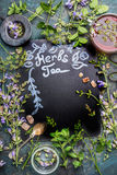 Lettering Herbal Tea on dark chalkboard. Various fresh herbs, tea tools and cup of tea on dark vintage background, frame, top view Stock Photos