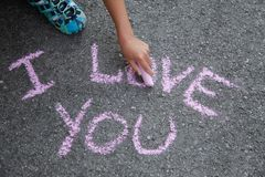 Lettering I love you with pink chalk on gray asphalt stock image
