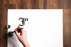 Lettering ink background. Painter`s hand draws. Lettering ink background. Unrecognizable painter`s hand draws word inspire with inks on white paper. Drawing Royalty Free Stock Photography