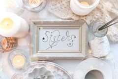 Lettering Inscription Sisters in white frame on shabby chic stylish background, feminity concept royalty free stock image