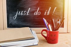 Lettering of inspirational quote JUST DO IT on black chalkboard. With red cup with pens and pencils, pile of notepads and papers. Motivation business office royalty free stock image