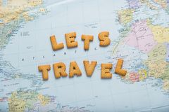 Lettering inspiring Let`s travel on map background! Preparing to journey. Lettering inspiring Let`s travel on map background! Preparing to journey stock image