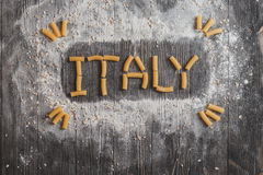 Lettering ITALY pasta on black rustic wooden background. Top view Royalty Free Stock Images