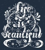 Lettering Life is beautiful with flowers, spray and swirls on a dark gray background Stock Image