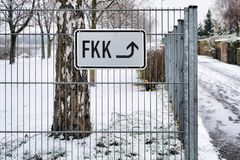 Lettering `nudist beach` on the fence at a bathing lake in Germany. In winter Stock Image