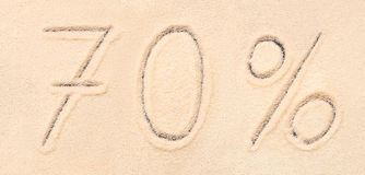 70 % lettering written on beach sand. 70 % lettering written on sand. Summer beach background Stock Image