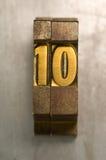 Letterpress 10. Brass / Gold colored letterpress piece on silver metal background royalty free stock image