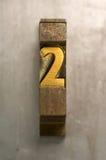 Letterpress 2. Brass / Gold colored letterpress piece on silver metal background royalty free stock image
