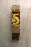 Letterpress 5. Brass / Gold colored letterpress piece on silver metal background royalty free stock photo