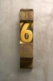Letterpress 6. Brass / Gold colored letterpress piece on silver metal background stock image