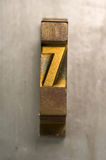 Letterpress 7. Brass / Gold colored letterpress piece on silver metal background royalty free stock photo