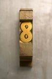 Letterpress 8. Brass / Gold colored letterpress piece on silver metal background stock photos