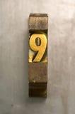 Letterpress 9. Brass / Gold colored letterpress piece on silver metal background stock photo