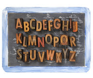Letterpress alphabet on blackboard Royalty Free Stock Images