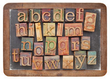 Letterpress alphabet on blackboard Stock Photography