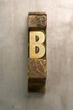 Letterpress B. Brass / Gold colored letterpress piece on silver metal background stock image