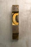 Letterpress C. Brass / Gold colored letterpress piece on silver metal background stock images