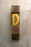 Letterpress D. Brass / Gold colored letterpress piece on silver metal background stock images