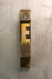 Letterpress E. Brass / Gold colored letterpress piece on silver metal background stock image