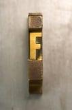 Letterpress F. Brass / Gold colored letterpress piece on silver metal background stock photos