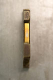 Letterpress I. Brass / Gold colored letterpress piece on silver metal background stock image