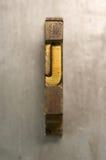 Letterpress J. Brass / Gold colored letterpress piece on silver metal background stock images