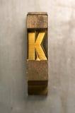 Letterpress K. Brass / Gold colored letterpress piece on silver metal background stock photos