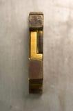 Letterpress L. Brass / Gold colored letterpress piece on silver metal background royalty free stock photography