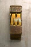 Letterpress M. Brass / Gold colored letterpress piece on silver metal background royalty free stock image