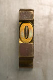 Letterpress O. Brass / Gold colored letterpress piece on silver metal background stock photography