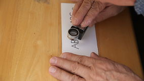 Letterpress printer checks work with magnifier Royalty Free Stock Photos