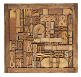 Letterpress printing blocks abstract. Box of vintage wood printing blocks - letters, numbers, symbols, punctuation marks, brass inserts Stock Images