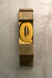 Letterpress Q. Brass / Gold colored letterpress piece on silver metal background stock images