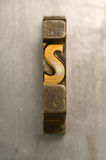 Letterpress S. Brass / Gold colored letterpress piece on silver metal background stock images