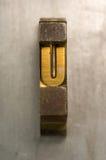 Letterpress U. Brass / Gold colored letterpress piece on silver metal background royalty free stock image