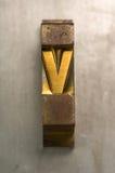 Letterpress V. Brass / Gold colored letterpress piece on silver metal background stock photo