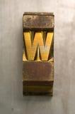 Letterpress W. Brass / Gold colored letterpress piece on silver metal background stock photos