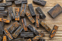 Letterpress wood type printing blocks. Vintage letterpress wood type printing blocks stained by inks placed randomly on a wooden table Stock Images