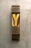 Letterpress Y. Brass / Gold colored letterpress piece on silver metal background stock photo