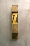 Letterpress Z. Brass / Gold colored letterpress piece on silver metal background stock photos