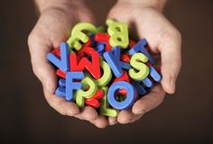 Letters. Man holding colorful plastic letters in his hands. Very short depth-of-field Stock Photos